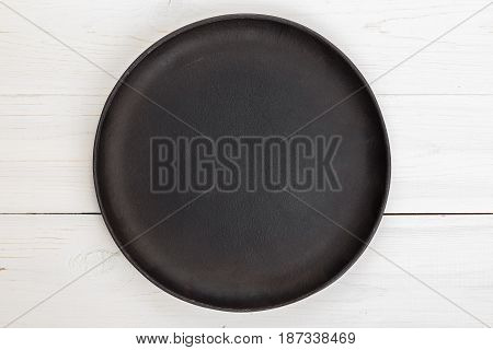 Empty round cast-iron frying pan for pizza or pie on a white wooden background space for text
