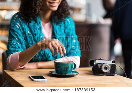 Joyful young woman is mixing hot beverage by spoon. She is sitting at table in cafeteria and laughing. Focus on blue cup. Retro camera and smartphone on table