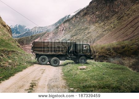 Truso Gorge, Georgia - May 22, 2016: Old Soviet Russian medium-duty truck Kamaz 53212 On Country Road In Summer Mountains Landscape In Truso Gorge, Kazbegi District, Mtskheta-Mtianeti Region, Georgia