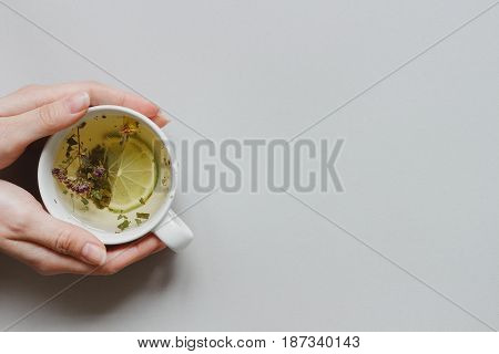 Tea Background. Hands Holding Cup Of Hot Green Tea On The Gray Background, Top View. Copy Space