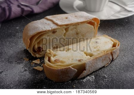Strudel with cottage cheese and raisins under powdered sugar on a slate surface