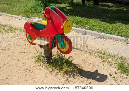 Red wooden motorcycle a swing. Children's playground