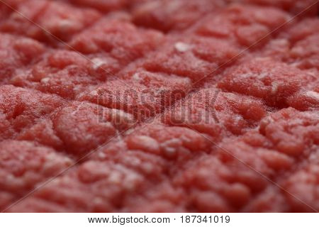 Texture of the surface of raw beef hamburger. Selective focus on the center