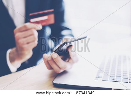 Closeup view of businessman holding credit card in hand and using smartphone, laptop computer on the wooden table.Blurred background.Horizontal