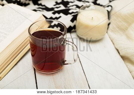 A cup of warm tea a warm blanket a candle and a book on a wooden background