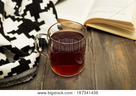 A cup of warm tea a warm blanket and an open book on a wooden background