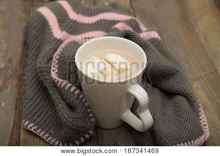 A cup of hot chocolate marshmallows knitted a warm blanket on a wooden background