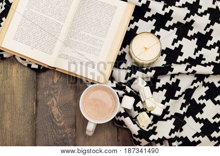 Hot chocolate marshmallow open book and candle on a wooden background. View from above
