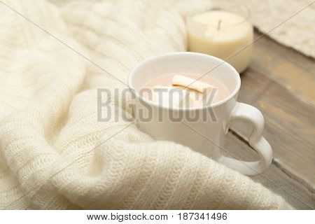 Hot chocolate marshmallow knitted warm plaid on a wooden background