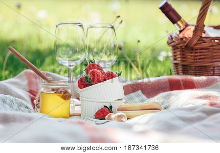 Two wine goblets fresh strawberry honey and wine are served for summer romantic picnic