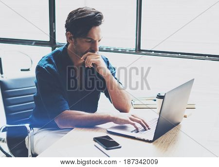 Young pensive man working at sunny office on laptop while sitting at wooden table.Businessman analyze stock reports on notebook computer.Blurred background, horizontal