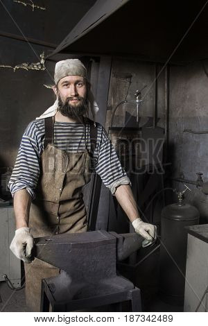 Blacksmith preparing to work metal with hammer on the anvil in the forge