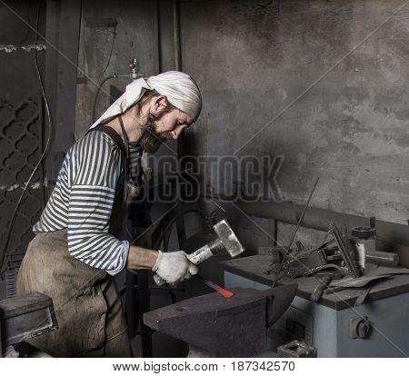 the senior blacksmith hammering a hot metal rod