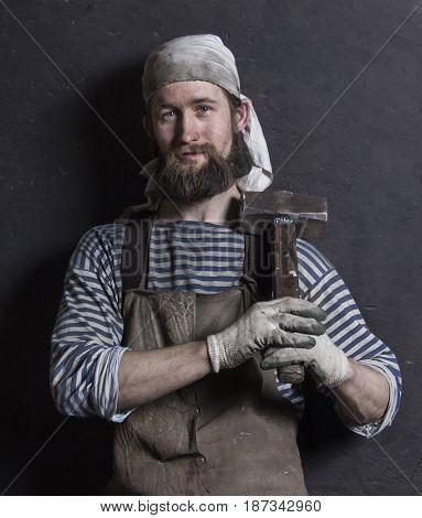 The portrait of senior blacksmith with sledgehammer