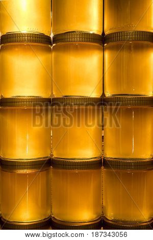 Golden yellow honey in glass jar on wooden board. Closeup. Copy space.
