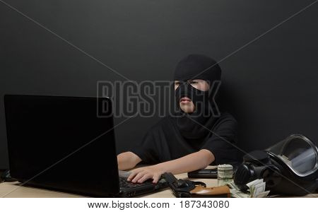 THE LITTLE BOY IN THE MASK OF THE TERRORIST BEHIND A LAPTOP