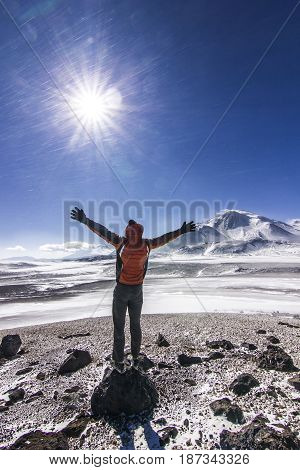 man standing with hands up on snow covered hill near ojos del salado volcano in chile with sun shining and blue sky