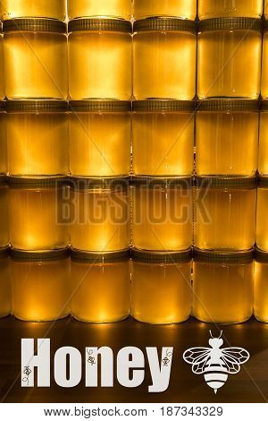 Golden yellow honey in glass jar on wooden board. Closeup. Copy space. with bee logo textspace