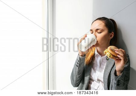 A young beautiful girl drinks coffee next to a window and eats a burger in a break between work.