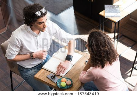 Do not look at this. Shy young man is closing sheet of paper in his notebook from girlfriend. They are sitting at table in confectionary shop. Top view