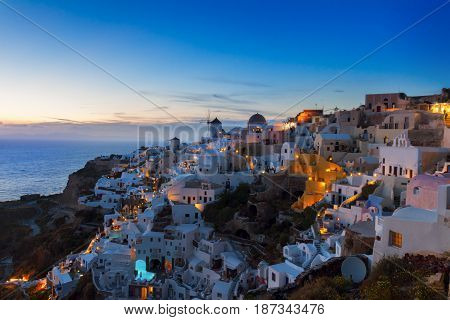 white houses Oia village illuminated at night, Santorini, Greece.