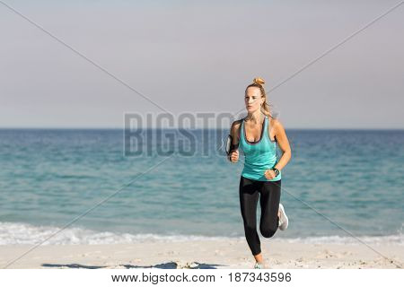 Full length of young woman jogging on shore at beach against sky