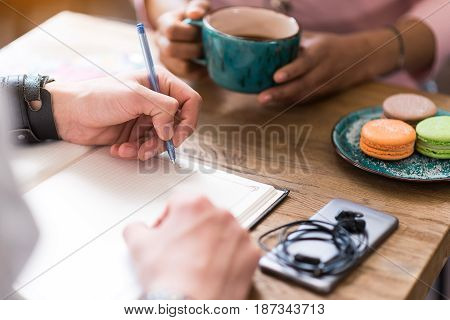 Close up of male hands writing in notebook while sitting at table. Woman is holding cup of coffee and eating macaroons