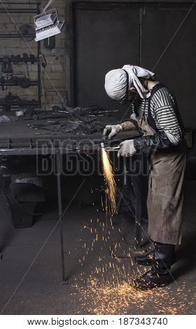 Young metalworker cutting on steel plate creating sparks, cutting iron with laser in workshop wearing protective goggles glasses and gloves