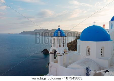 traditional greek village Oia of Santorini, with blue domes of churches in sunset light, Greece