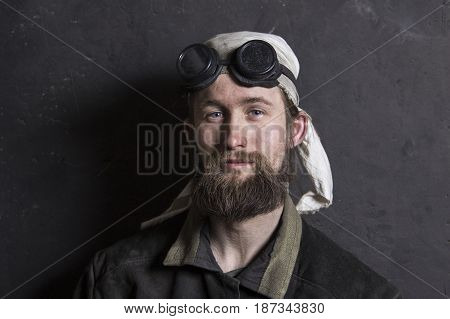 the portrait of Young metalworker wearing protective goggles glasses and gloves