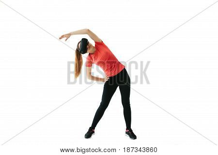 A young beautiful woman in virtual reality glasses makes aerobics remotely. Future technology concept. Classes in single sports remotely. On a white background.