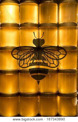 Golden yellow honey in glass jar on wooden board. Closeup. Copy space. with bee logo