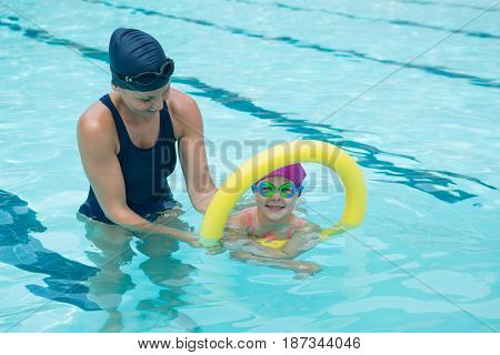Female instructor training young girl in pool at leisure center