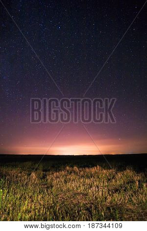 Purple Night Starry Sky Above Field And Yellow City Lights On Background. Night View Of Natural Glowing Stars