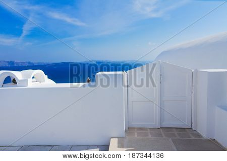White gates against volcano caldera and sea, beautiful details of Santorini island, Greece