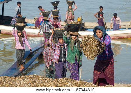 BAGAN, MYANMAR - DECEMBER 23, 2016: Burmese girls unload the barge with the river gravel