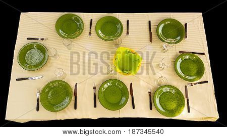 Green cutlery set on table ready for food to be served isolated on black.