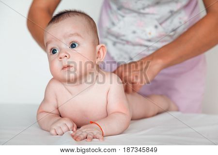 Woman doctor doing back massage to baby. Children's massage.