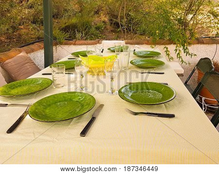 Green dishes on table ready for food to be served at lunch time.