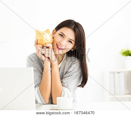 smiling young asian woman holding piggy bank