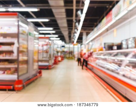 Abstract blurred supermarket aisle with colorful shelves with refrigerator as background