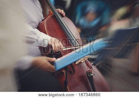 A blurred picture of a man playing the cello