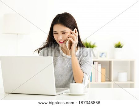 young Woman working on laptop and talking on the phone