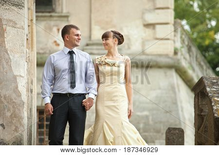 Happy Man Holds Woman's Hand Standing On The Ruins
