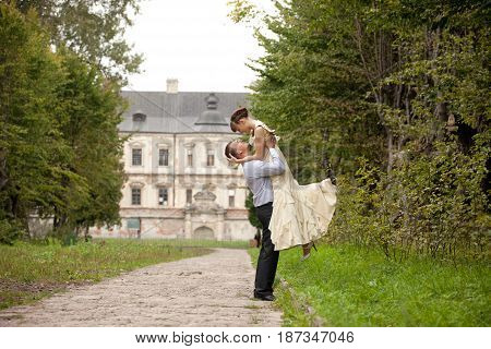 Happy Man Raises A Lady Up Standing On The Path In Park