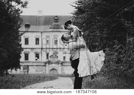 Man Raises Lady Up Posing In The Old Garden