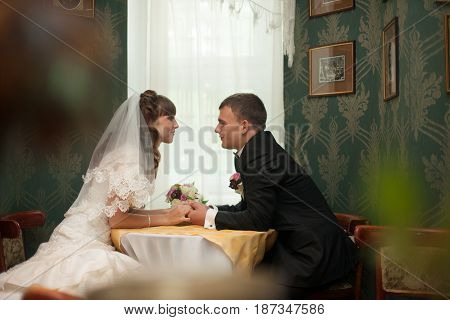 Wedding Couple Sits At The Coffee Table In The Green Hall