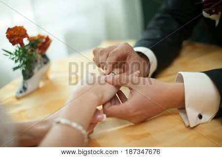 A Closeup Of Bride's Hands Lying Over The Tea Table While Groom Adjusts On Her A Wedding Ring