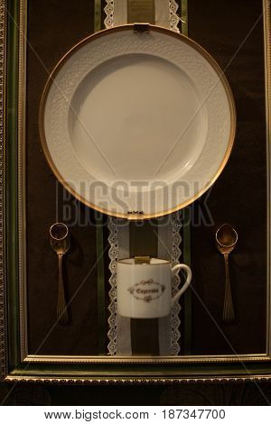 Tea service put in the frame and wedding rings put over spoons
