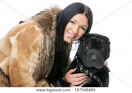Beautiful brunette young woman in fur coat sitting with black adult shar pei dog